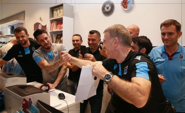 BAŞKAN TAKIM ELBİSEYİ NASIL KAYBETTİ  Trabzonspor'da renkli görüntüler yaşanmaya devam ediyor. Trabzonspor başkanı Ahmet Ağaoğlu'nun Kulüp çalışanları, Teknik ekip, futbolcular ve taraftarla kurduğu diyaloglar herkes tarafından olumlu karşılanıyor. Başkan son 2 gündür forma ve kombine satmak için bizzat kendisi kasaya geçiyor. Dün de Akyazı'da ki TSClub noktasındaydı. Taraftarların ilgi gösterdiği organizasyonda hem satış yaptı, hem imza dağıttı hem de taraftarlarla bol bol fotoğraf çektirdi. En ilginç an ise tüm takımın ve Teknik Direktör Ünal Karaman'ın organizasyon anında mağazan içeri girmesiydi. Bu hem başkanı hem de taraftarı şaşırtsa da yapılan sürprizle beraber coşku yaşandı. Daha sonra futbolcular 2661 forma alarak takıma katkı yaptıklarını belirttiler. Kaptan Sosa listenin altına imzasını atarak olayı resmileştirdi. Ancak bu ziyaretin altında çok ilginç bir iddia olduğu sonradan ortaya çıktı. Trabzonspor Genel Müdür Yardımcısı Ulaş Özdemir, Başkan Ağaoğlu'na Akyazı'daki organizasyonda 2 bin forma satacaklarına inandıklarını söylüyor. Başkan da buna ihtimal vermiyor tabi. İddiaya giriyorlar takım elbisesine. Ulaş Özdemir bu. Kendini sağlama almadan hiçbir işe girmez. Önceden ayarladığı organizasyon ile tüm futbolculara toplamda 2661 formayı çoktan satmıştı bile. Bu konudan haberi olmayan başkan takım elbiseyi daha organizasyon başlamadan kaybetmişti ama bu acı gerçeği organizasyon sırasında öğreniyor. Bakalım başkan Ağaoğlu , Özdemir'e takım elbiseyi alacak mı? Merakla bekliyoruz.