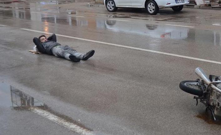 Islak asfaltta yatarak ambulans bekledi