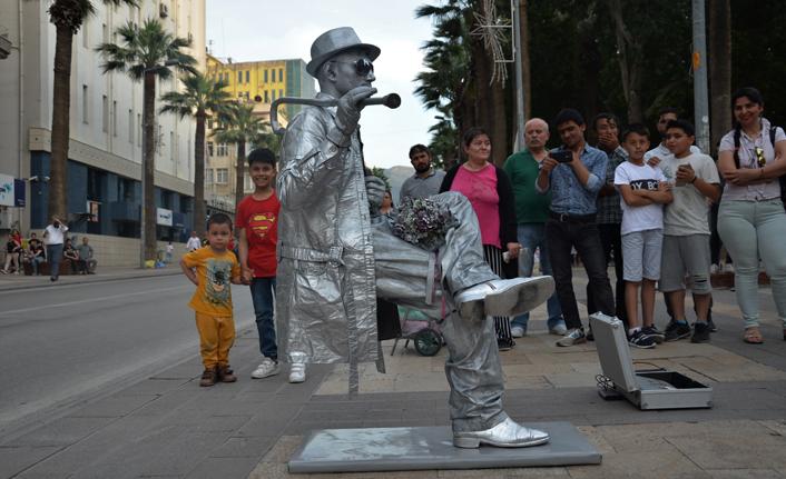 Tek ayağının üstünde oturan heykel adam görenleri şaşırttı